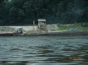 Rock being dumped into a barge for use in rock structures, wingdams, etc, to maintain the channel and direct water flow