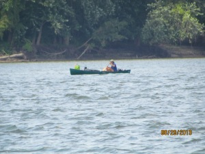 Canoer on lake, having a tough time into wind and waves, but he is making headway.