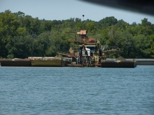 Sand and gravel being taken from the river,  pumped out with dredge, and then run thru screens to sort into proper sizes,  looks like 3-4 inch rock being loaded onto barge
